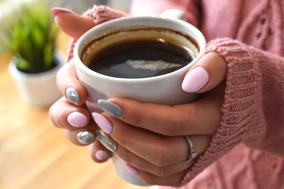 pomalowane paznokcie na kubku z kawą